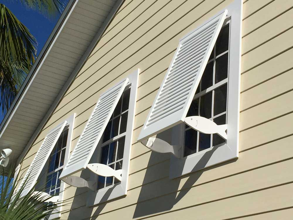 Fixed tropical exterior bahama shutters with cutout fish supports.