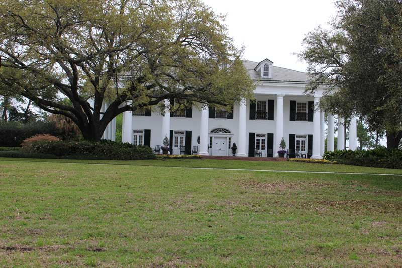 White plantation home with black New Orleans shutters.