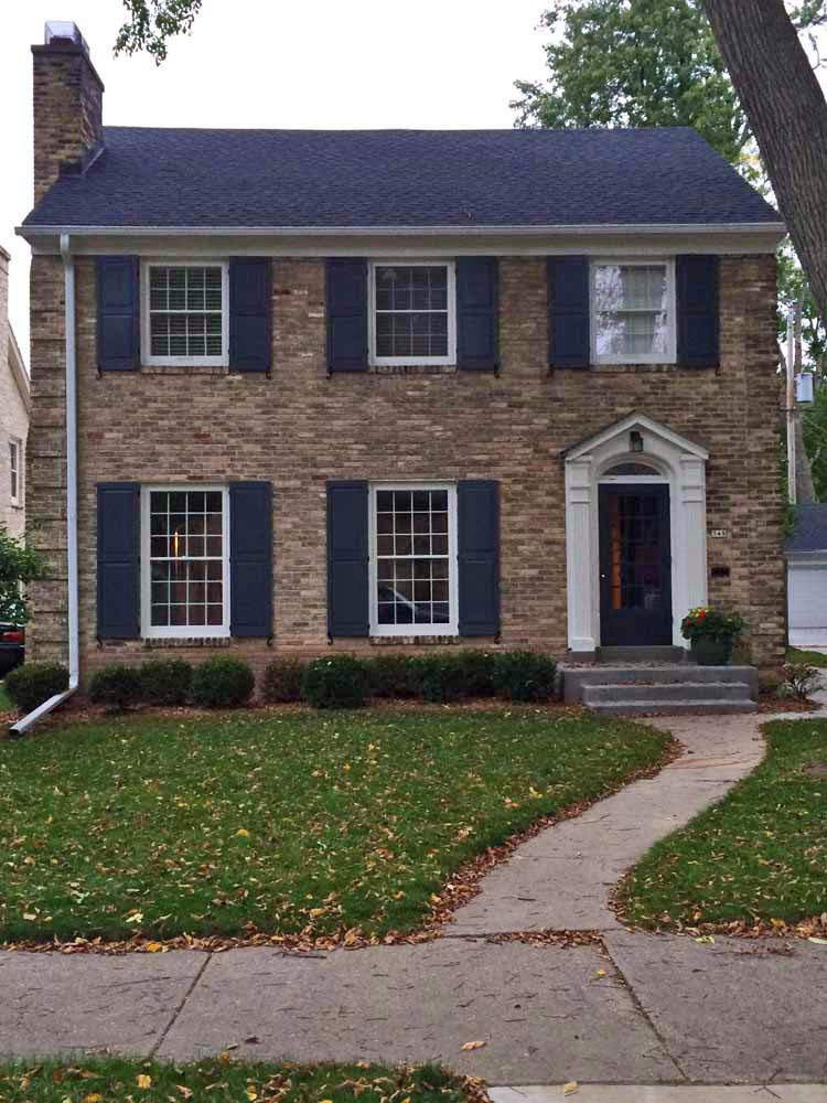 Brick house with black raised panel exterior composite shutters.