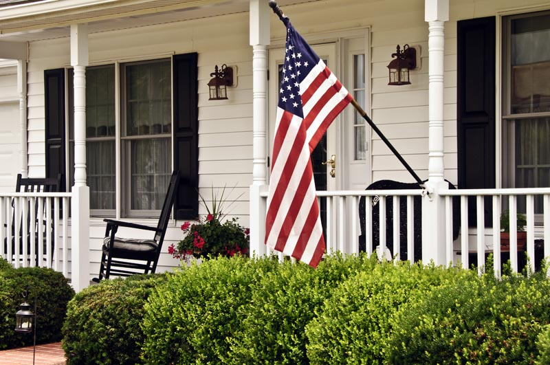 Black exterior American shutters on the porch with an American flag.