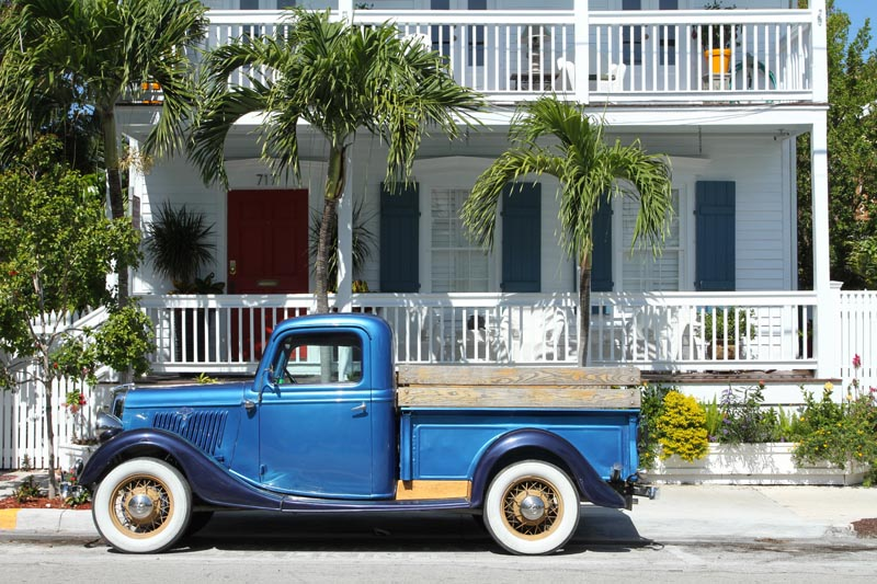 Florida Keys shutters installed on a white house with blue truck.