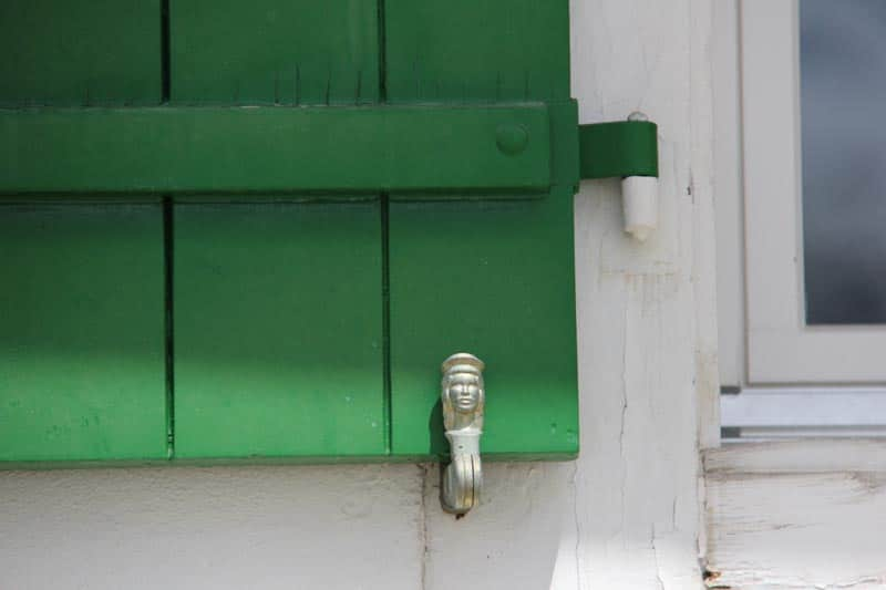 French lady shutter dog with green farmhouse shutter.