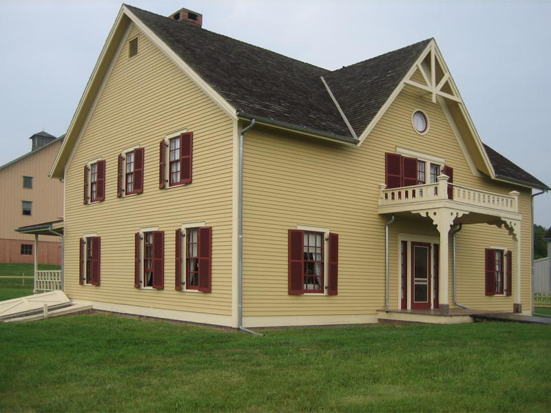 Yellow house on a traditional farm with red exterior shutters.