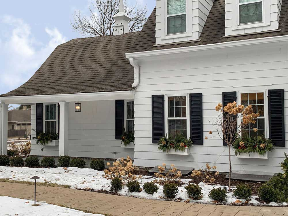 Black modern farmhouse shutters installed on white exterior siding.