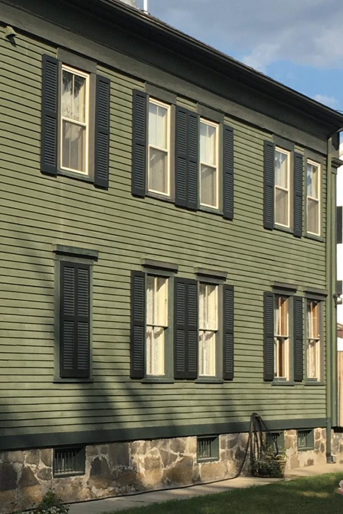 Dark green shutters installed on a house with green siding.