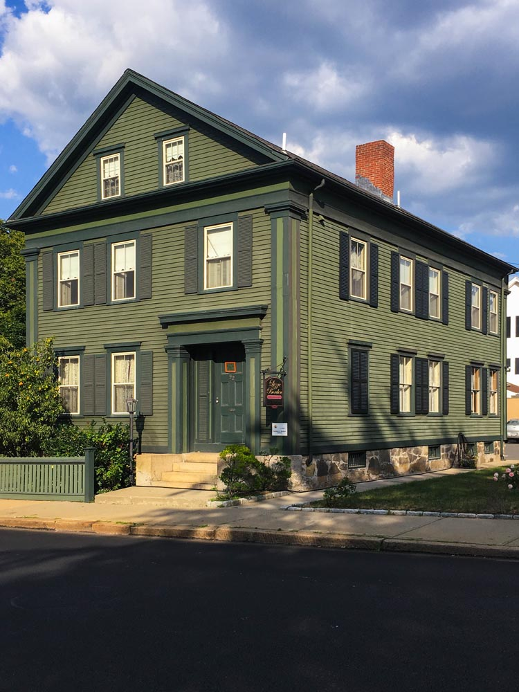 Lizzie Borden house with wood louvered green shutters.