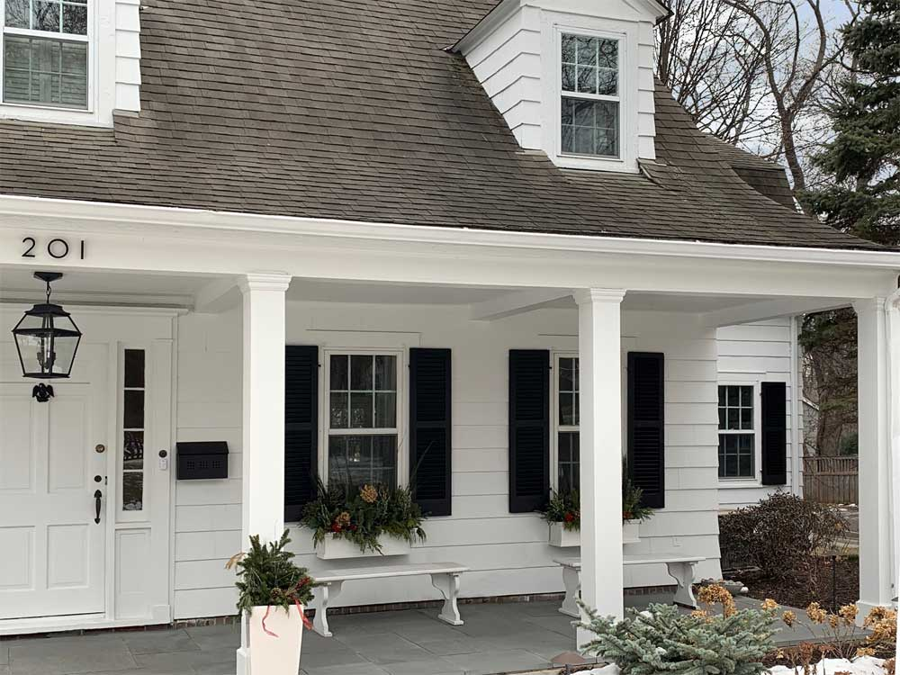 Outdoor famhouse shutters installed on porch.