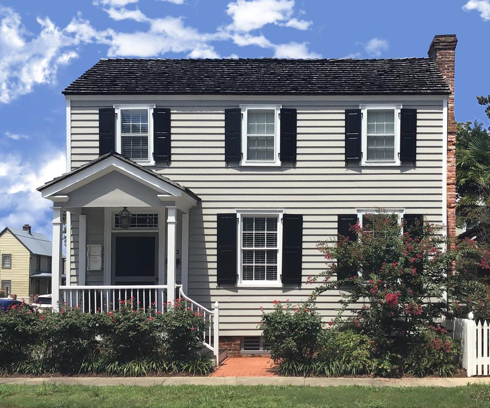 Black raised panel custom exterior shutters installed on a two-story house.