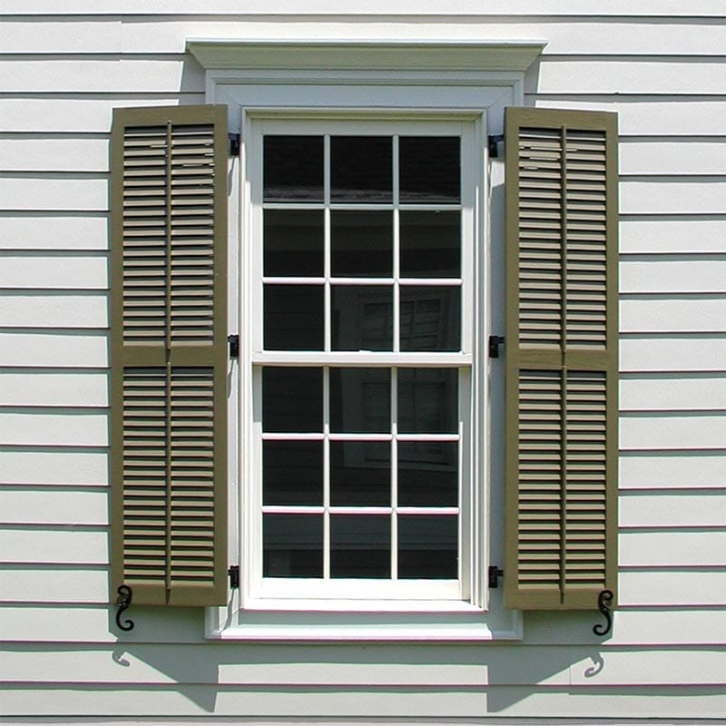Louvered wood exterior shutters with faux tilt bar.