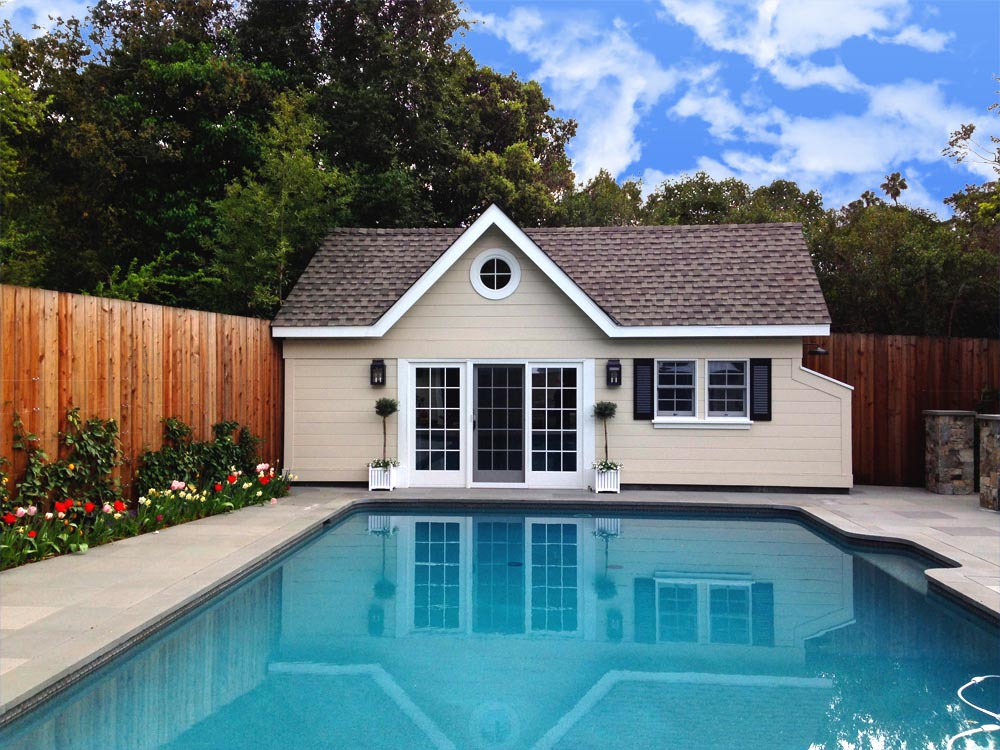 Pool house with fence, flowers, and louvered window shutters.