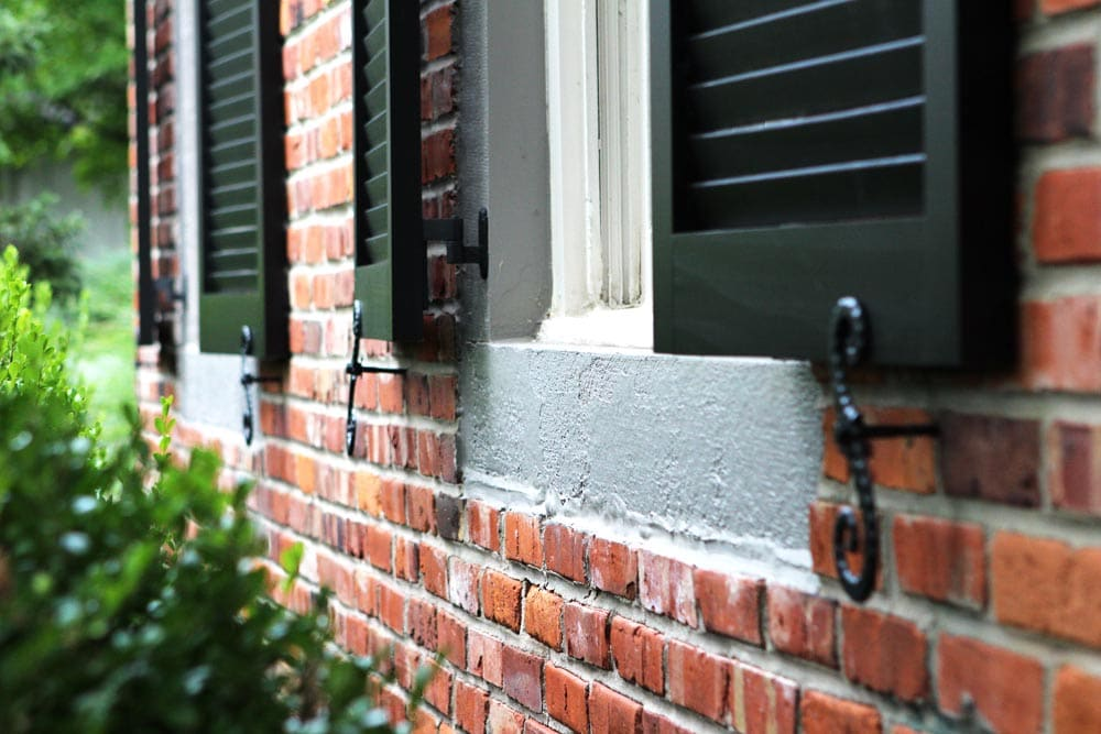 Black wood exterior shutters with s-pattern shutter dogs.