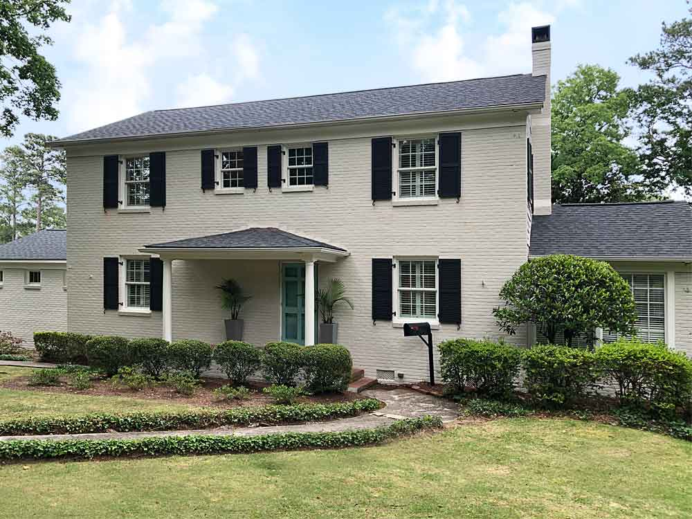 Exterior black shutters with slats installed on a white brick house.