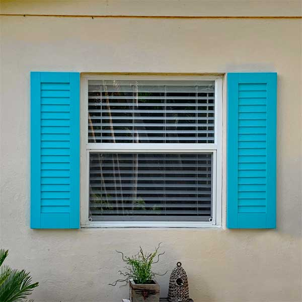 Outdoor composite louvered shutter installed on a double-hung window.