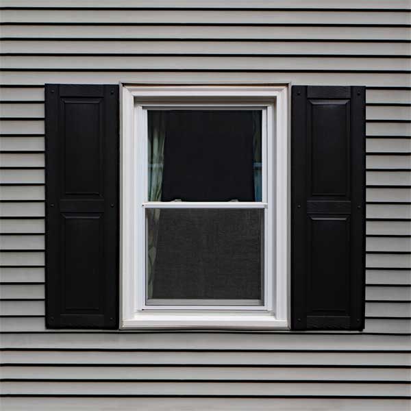 Outdoor vinyl raised panel shutters installed.