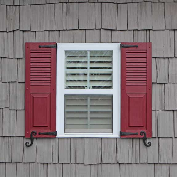 Outdoor vinyl shutters with louvers and raised panels installed on an exterior house window.