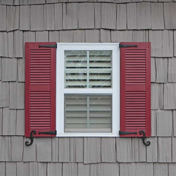 Louvered outside vinyl shutter installed on an exterior house window.