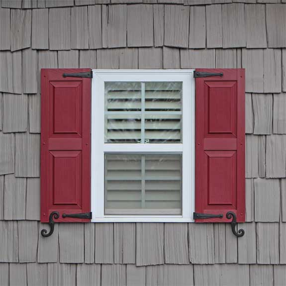 Raised panel outdoor vinyl shutters installed on an exterior house window.