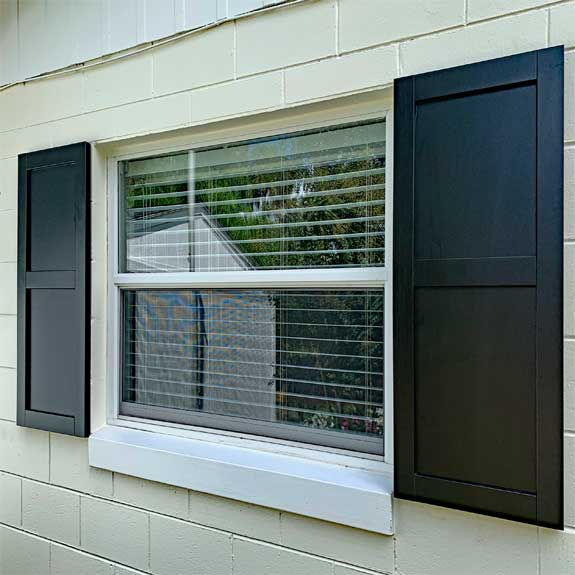 Black exterior composite solid flat panel shutters.