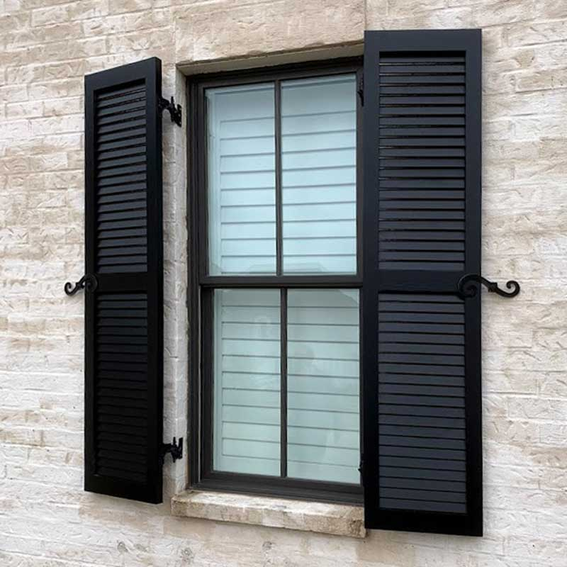 Black louvered shutters installed on a stone window.