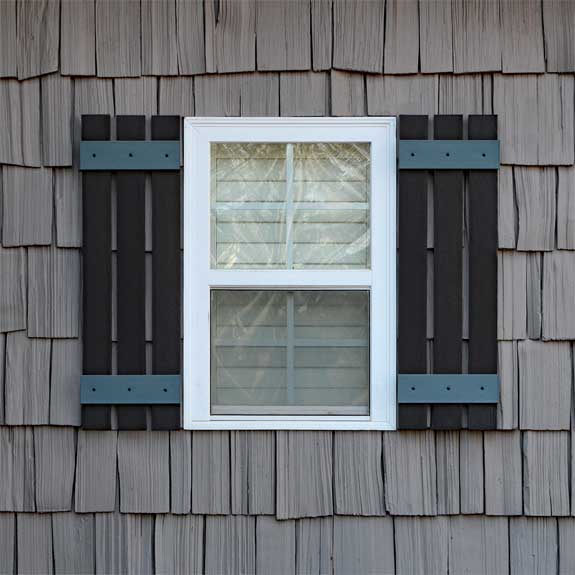 Installed vinyl board and batten exterior shutters on a window.