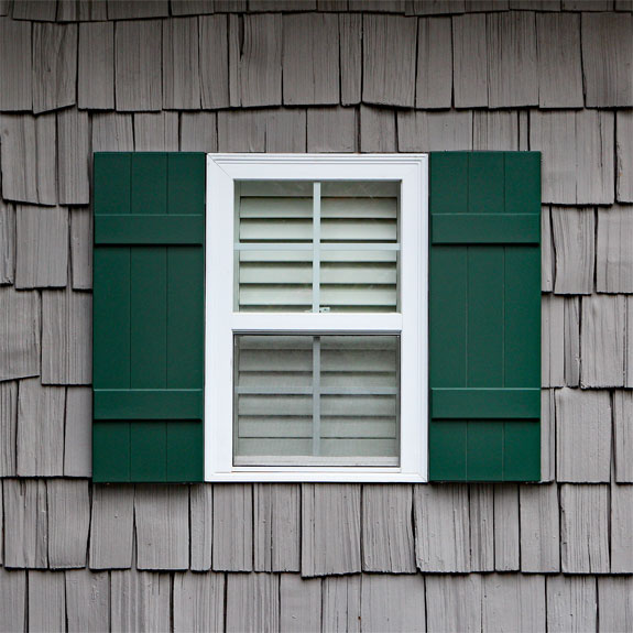 Green composite board and batten shutters installed.