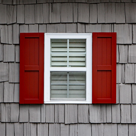 Red composite shaker style exterior shutters.