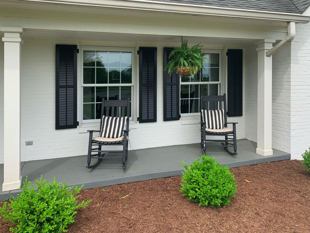 Black composite louvered shutters with faux tilt bar.