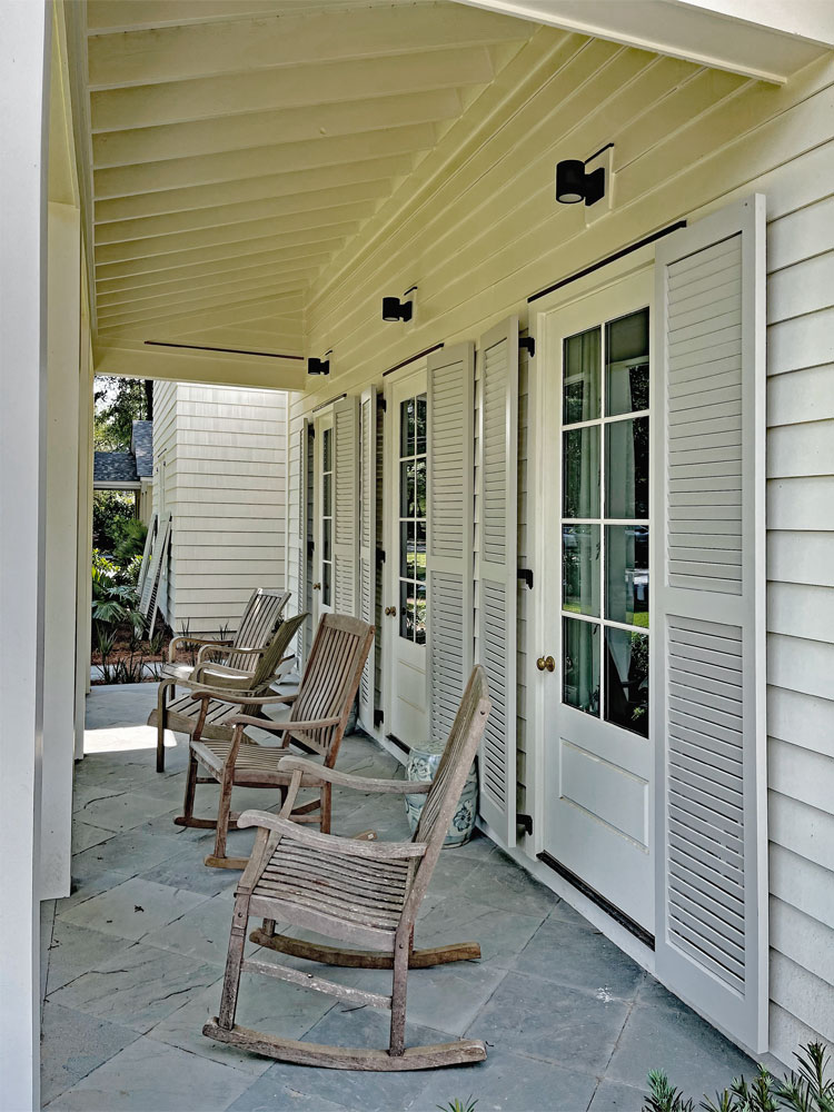 Outdoor front porch with rocking chairs and exterior shutters.