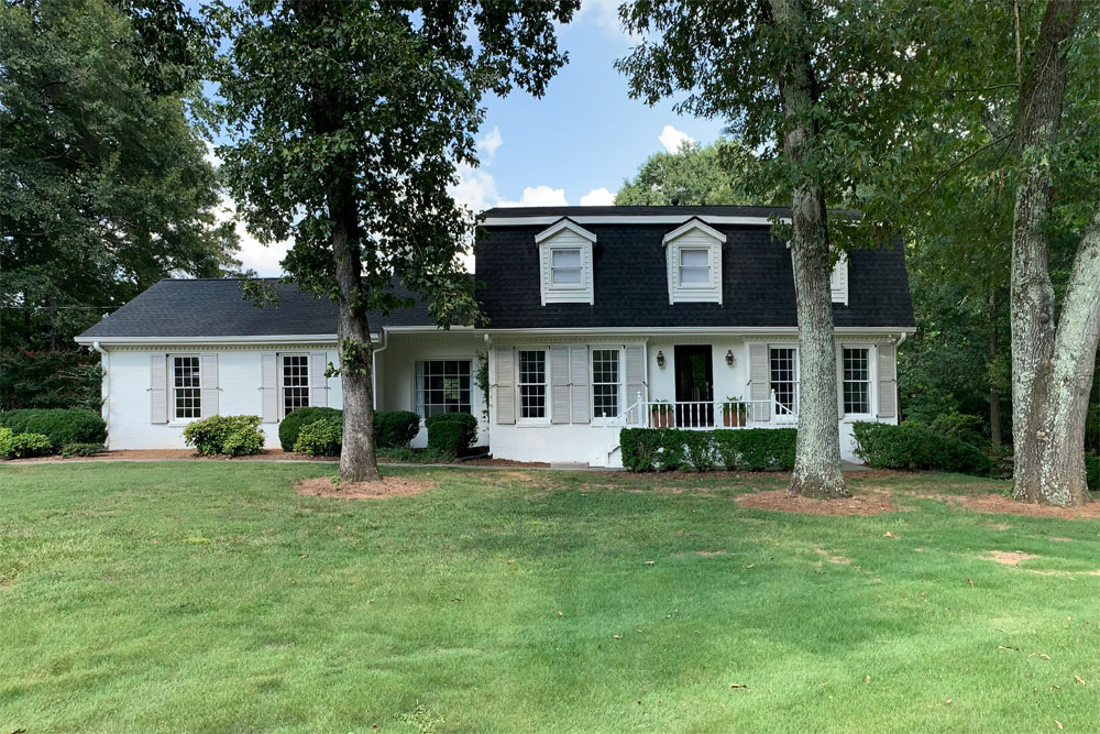 Outdoor white house with gray shutters installed.
