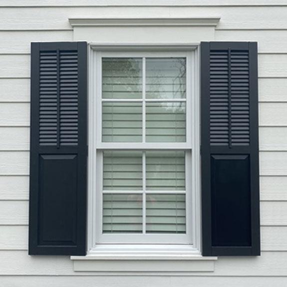 Black combo composite exterior window shutters.